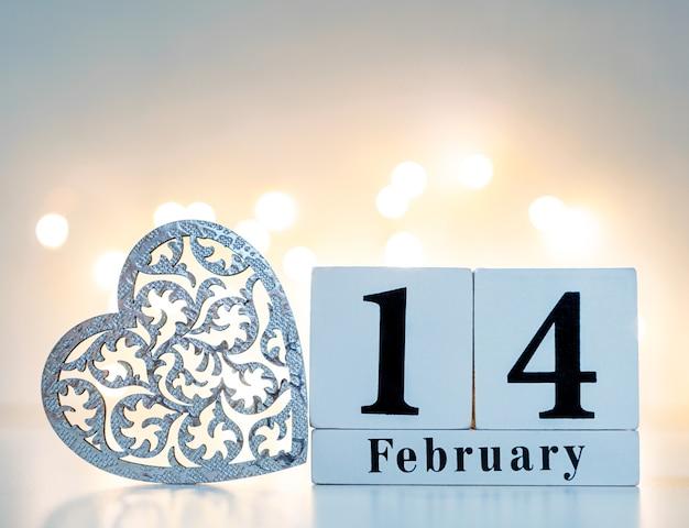 Show de calendário de madeira de 14 de fevereiro com coração de madeira e bokeh dourado na parte de trás. conceito de dia dos namorados.