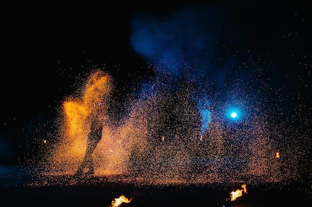Show de fogo, dançando com chamas, mestre masculino fazendo malabarismo com fogos de artifício, performance ao ar livre, desenha uma figura de fogo no escuro, faíscas brilhantes à noite. um homem em um terno led dança com fogo.