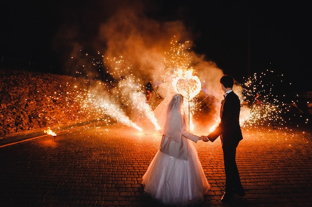 Show de fogo de casamento e coração de fogo à noite na superfície preta