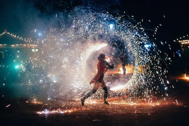 Show de fogo. garota gira tochas brilhantes de fogo