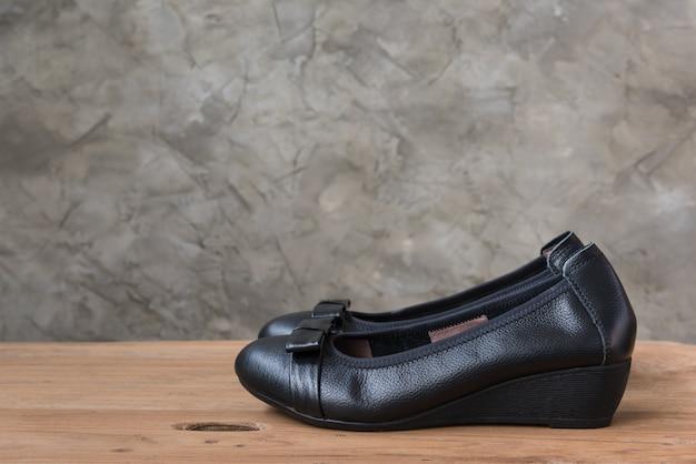 Show de sapatos pretos femininos na mesa de madeira antiga