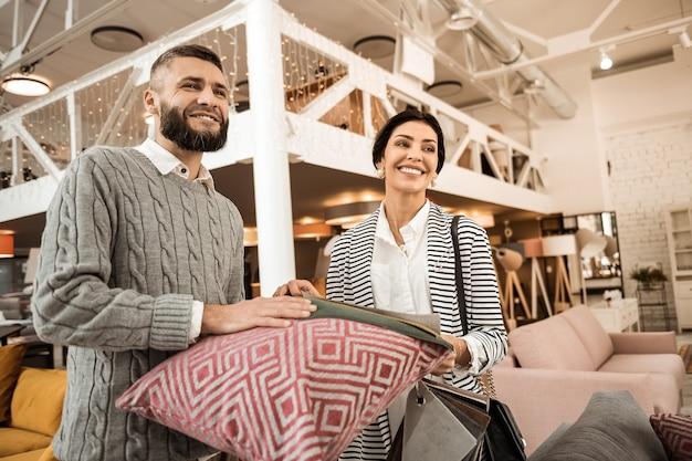 Showroom com mobília. jovem família alegre e positiva carregando travesseiros e materiais enquanto escolhe o equipamento para a sala de estar