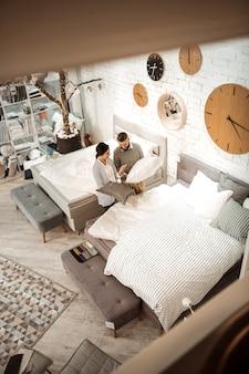 Showroom da moda. casal de cabelos escuros carregando travesseiros fofos e discutindo compras em frente à cama king-size