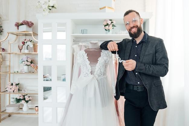 Showroom de roupas. designer de moda masculina apresentando vestido puro no manequim.