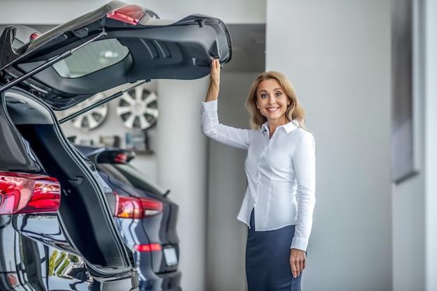 Showroom. mulher bonita loira em pé perto do carro vermelho com o capô do motor aberto