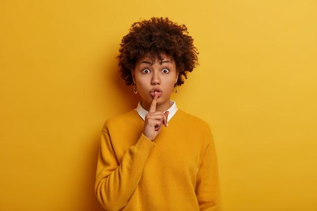 Shush, fique quieto. mulher afro-americana maravilhada misteriosa faz sinal de silêncio, pede para ficar em silêncio, conta informações ou histórias muito secretas ao interlocutor, veste um suéter amarelo brilhante, espalha boatos.