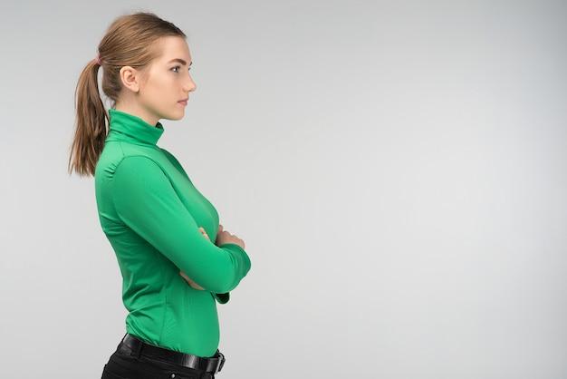 Sideview do close up de uma jovem mulher triste que está com os braços dobrados isolados no fundo. - imagem