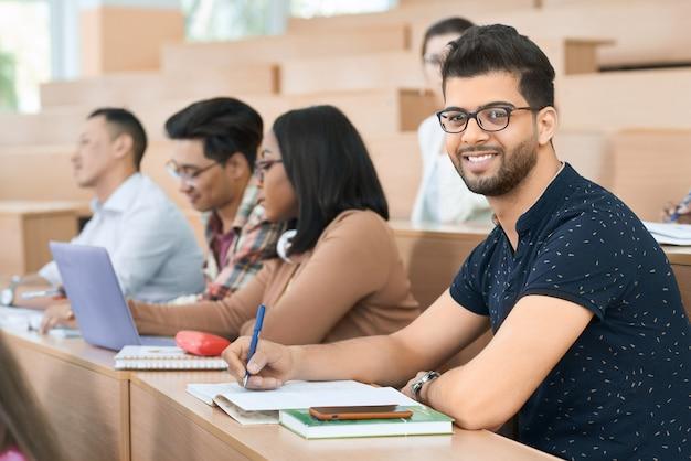 Sideview do estudante árabe que senta-se na universidade e que olha a câmera.
