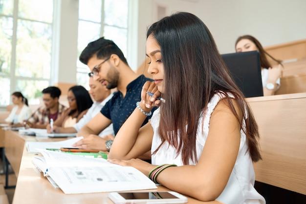 Sideview do estudante novo que prepearing para exames na universidade.