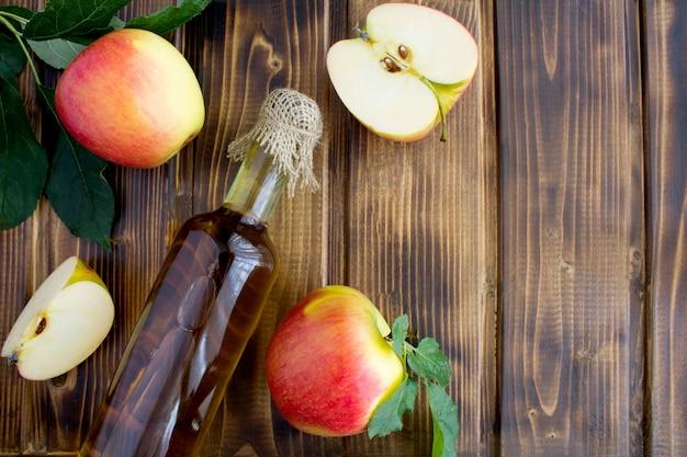 Sidra de vinagre de maçã na garrafa de vidro na superfície de madeira marrom.