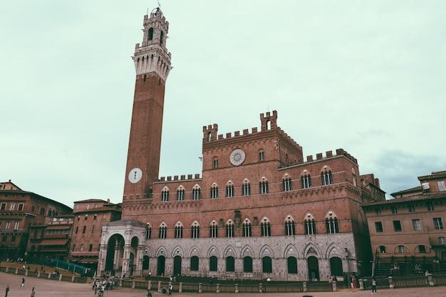 Siena, itália - 28 de junho de 2018: vista panorâmica do palazzo pubblico (câmara municipal) é um palácio e torre del mangia é uma torre na cidade na piazza del campo. dia ensolarado de verão e céu azul dramático