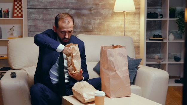 Siga a foto do empresário caucasiano com fome de terno com comida para viagem.