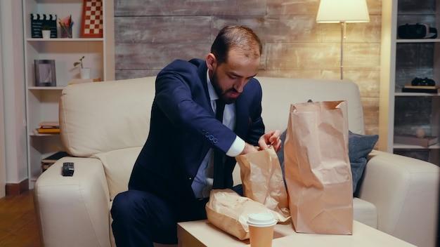 Siga a foto do empresário faminto chegando em casa com comida para viagem.