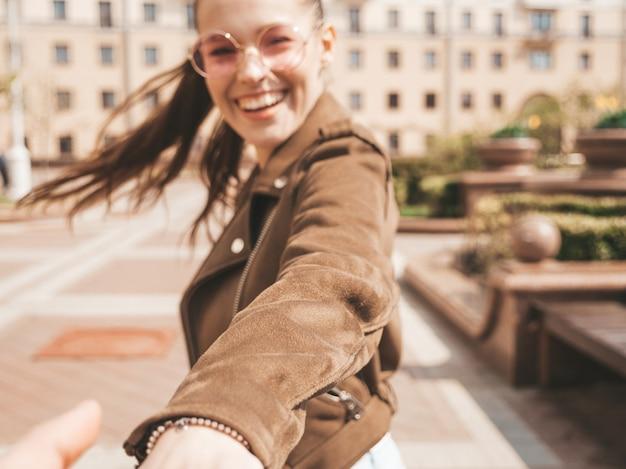 Siga-me conceito romântico jovem mulher com cabelos longos ao ar livre, segurando a mão do namorado