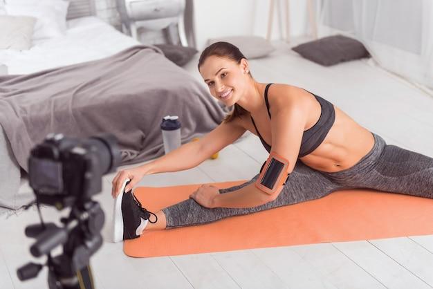 Siga meu exemplo. atraente exuberante jovem blogueira de cabelos escuros sorrindo e praticando esportes enquanto está sentada no tapete e fazendo um vídeo para seu blog