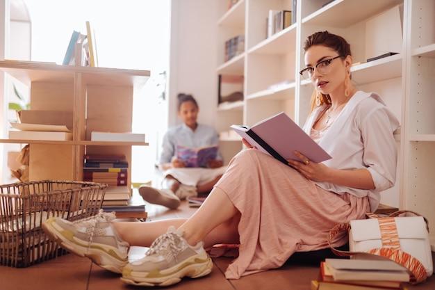 Siga meu exemplo. menina encantadora segurando um livro com as duas mãos enquanto lê um artigo útil