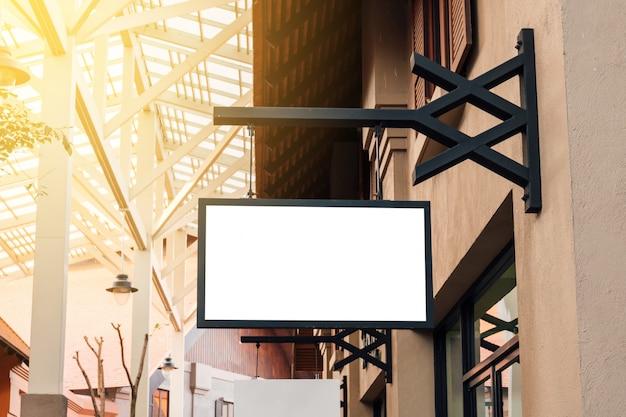 Signage vazio preto horizontal na parte dianteira da loja de roupa com espaço da cópia.