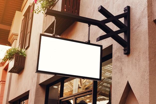Signage vazio vazio horizontal na parte dianteira da loja de roupa com espaço da cópia.