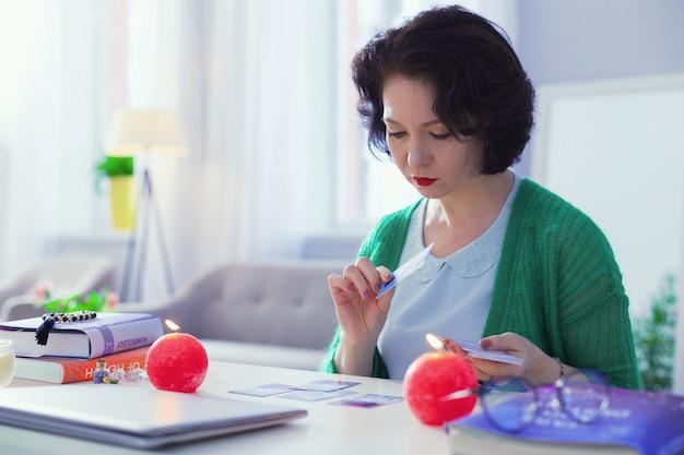 Significado especial. bela mulher séria olhando para as cartas de tarô enquanto interpreta seu significado