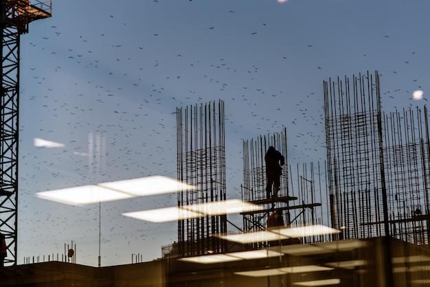Silhouette engenheiro da indústria da construção ordens permanentes para a equipe do trabalhador para trabalhar a segurança em terrenos altos sobre o fundo borrado pastel do sol
