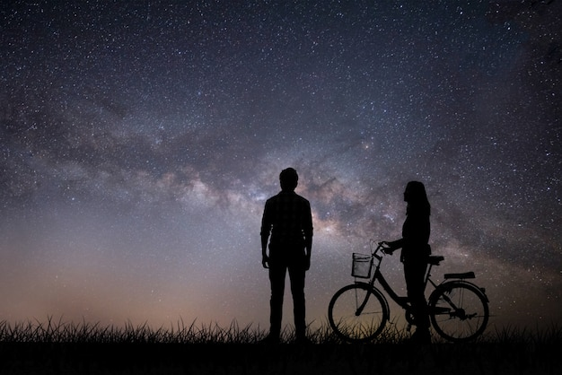 Silhouette, jovem casal apaixonado, aproveite o bom tempo juntos durante o pôr do sol.