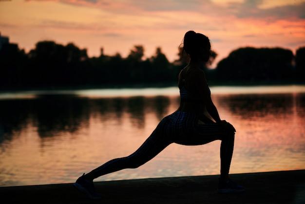 Silhoutte de exercitar a mulher perto do lago da cidade no por do sol.