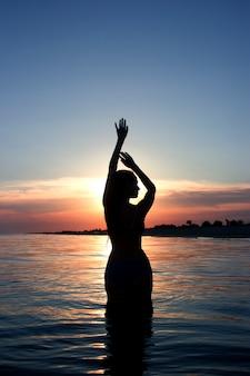 Silhueta ao pôr do sol de uma bela fibra feminina na água do mar