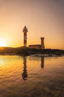 Silhueta ao pôr do sol do farol de toston, punta ballena, perto da cidade de el cotillo, ilha de fuerteventura, ilhas canárias. espanha
