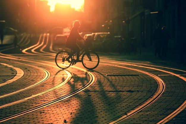Silhueta borrada de bicicleta de equitação de mulher durante o pôr do sol na cidade de bordeaux em estilo vintage