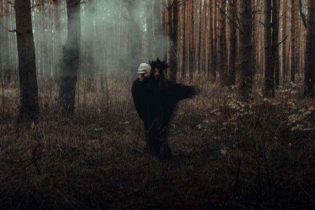 Silhueta borrada de uma bruxa negra malvada com uma caveira nas mãos realizando um ritual satânico oculto em uma floresta escura e sombria