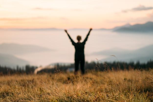 Silhueta borrada de uma mulher nas montanhas.