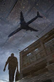 Silhueta borrada do reflexo de uma pessoa caminhando sozinha na calçada molhada da cidade em um dia chuvoso