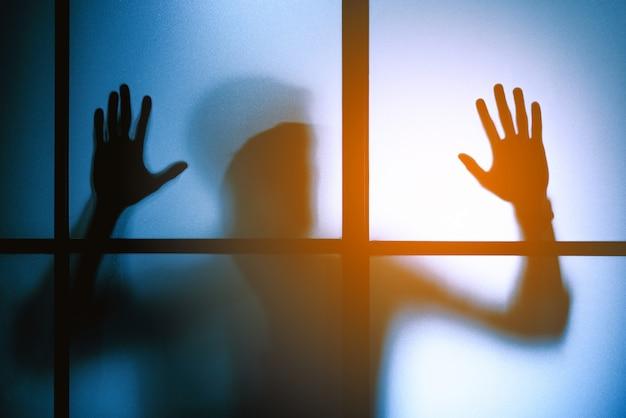 Silhueta com medo homem ficar atrás da porta de vidro