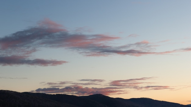 Silhueta crepuscular de montanhas com belas nuvens ao pôr do sol