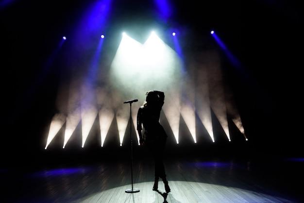 Silhueta da cantora no palco. fundo escuro, fumaça, holofotes.