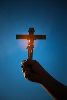 Silhueta da cruz na mão, símbolo de religião na luz e na paisagem sobre um nascer do sol, fundo, religioso, conceito de fé