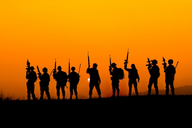 Silhueta da equipe de soldado no céu pôr do sol. soldado com patrulha de metralhadora