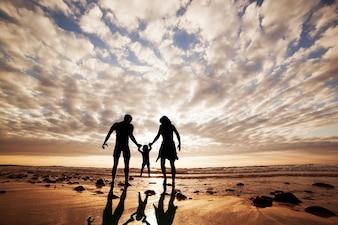 Silhueta da família que joga na praia