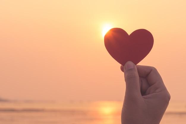 Silhueta da mão que prende o coração vermelho durante o fundo do por do sol.
