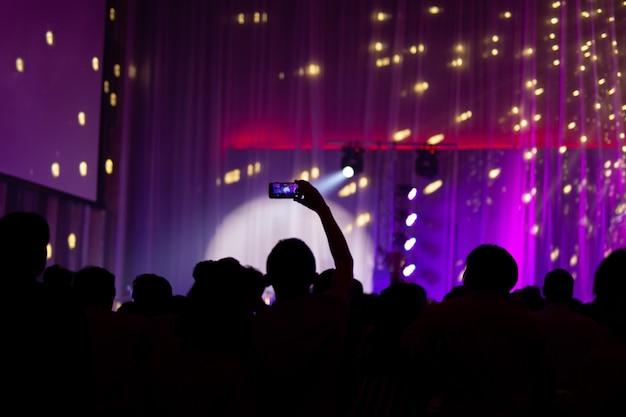Silhueta da mão que toma imagens do telefone celular no concerto vivo borrado.