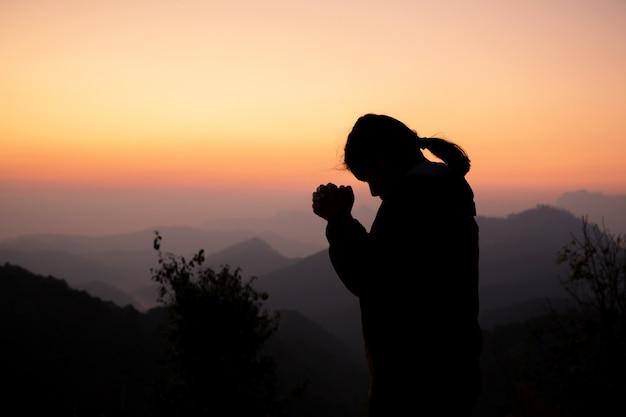 Silhueta da menina que reza sobre o fundo bonito do céu.