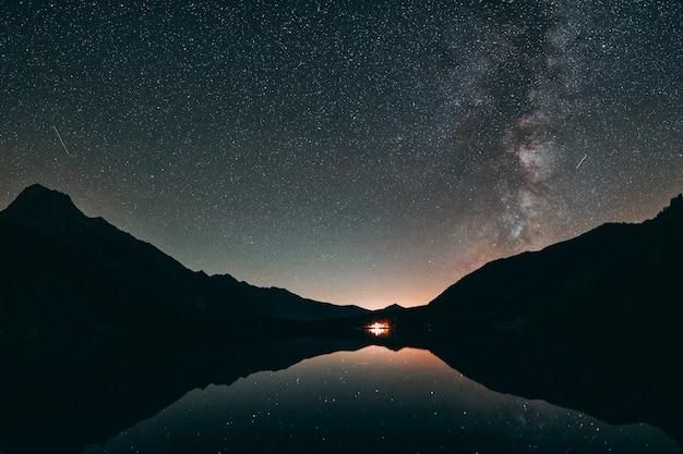 Silhueta da montanha e corpo de água calmo