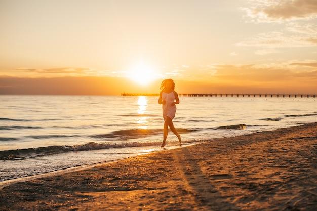 Silhueta da mulher bonita magro nova na praia do por do sol.