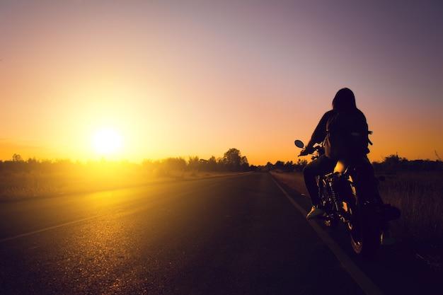 Silhueta da mulher do motociclista com sua motocicleta (motocicleta) na rua, ele trouxa do ombro.