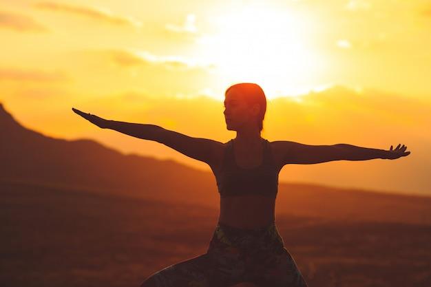 Silhueta da mulher nova que pratica a ioga ou os pilates no por do sol ou no nascer do sol no lugar bonito da montanha.