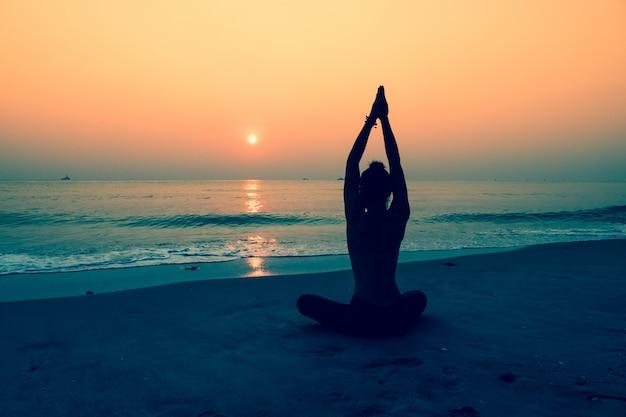 Silhueta da mulher que faz a ioga em uma praia