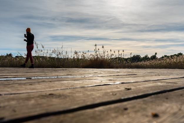 Silhueta da mulher que toma uma foto com seu móbil de uma paisagem mediterrânea.