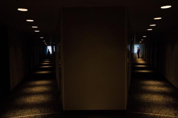 Silhueta da noiva e do noivo no corredor escuro
