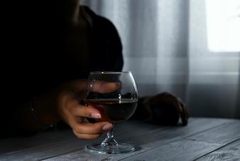 Silhueta da pessoa alcoólica anônima da mulher que bebe atrás do vidro do álcool.