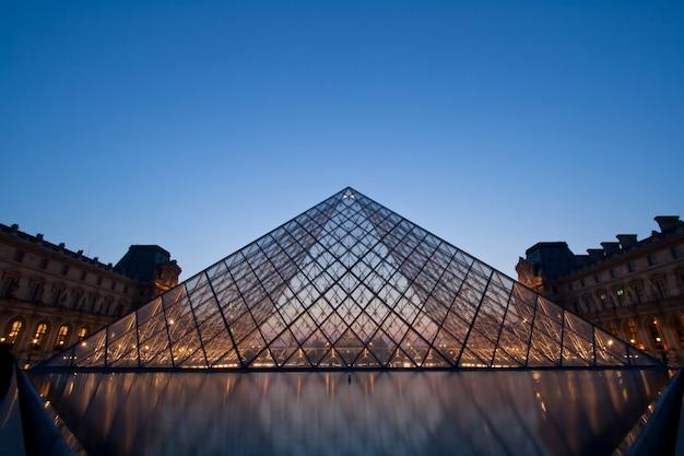 Silhueta da pirâmide do louvre à noite durante a exposição de antiguidades de verão